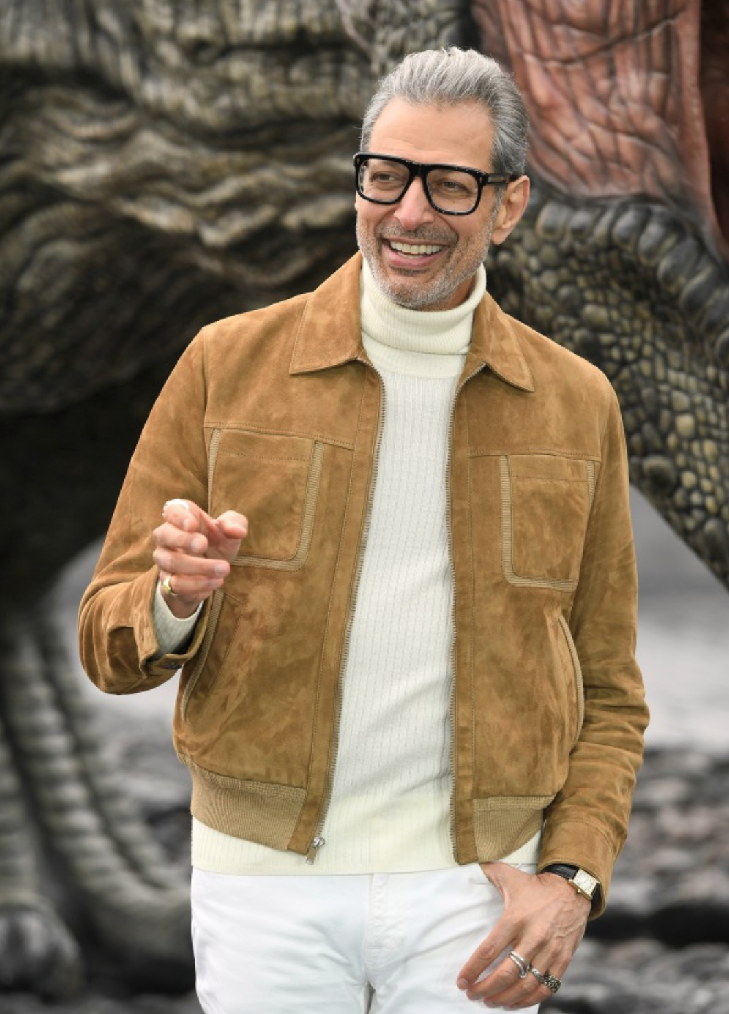 Actor Jeff Goldblum wearing a cream colored turtleneck sweater and brown suede jacket